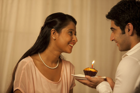 Pleased young woman looking at man while holding cupcake