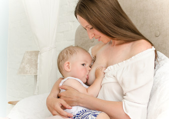 Breastfeeding. Young mother nursing baby. Family at home