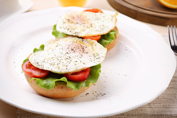 Plate with delicious egg sandwiches on table