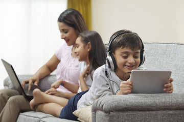 Focused boy using digital tablet headphones with mother and sister using laptop in background