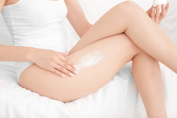 Woman sitting on sofa and applying cream onto her leg