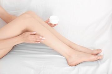 Woman sitting on sofa and applying cream onto her leg