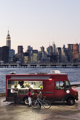 A group of people ordering Pizza from a Food Truck with Manhattan in the background