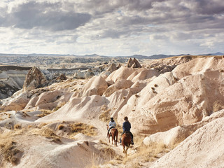 Two horse riders traveling through vast landscape with deep canyon walls and curious rocky formations.