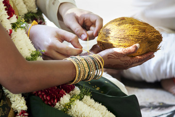 Groom tying string around bride's wrist with bracelets and coconut