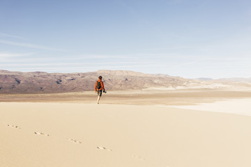 young man hiking up the Eureka Sand Dunes in desert setting in Death Valley National Park