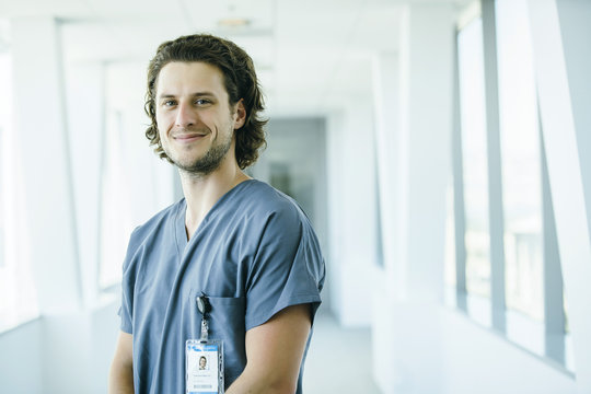 Portrait of confident, happy male nurse in hospital hallway