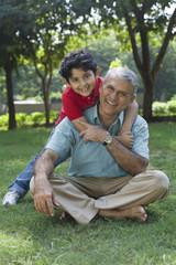 Portrait of grandson hugging grandfather in park