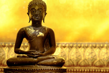 Buddha statue of meditation pose in peaceful atmosphere. Golden background is part of huge reclining Buddha statue in a famous temple in  Bangkok , Thailand and popular tourist place