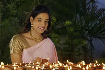 Young woman arranging diyas