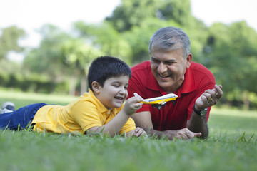 Grandfather watching grandson play with toy aeroplane
