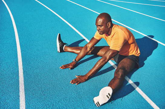 Young runner stretching on a running track before training
