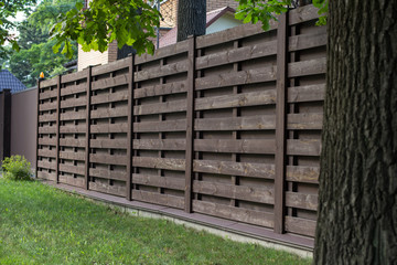 Wooden fence in Scandinavian style, on a green lawn