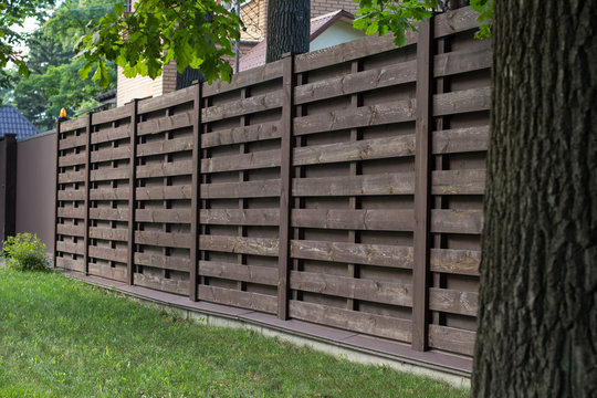 Wooden fence in Scandinavian style, on a green lawn