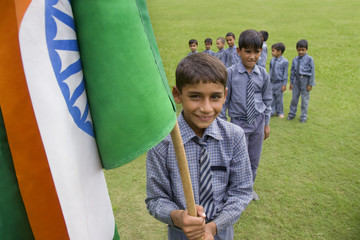 Portrait of a school boy holding the Indian flag