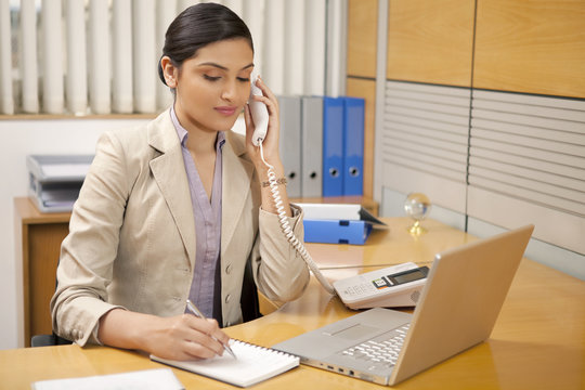 Female executive taking notes while on call