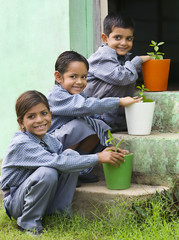 School kids with colored potted plants