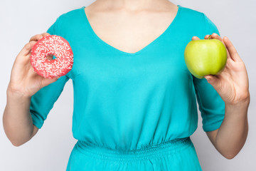 Beautiful young woman in green dress holding apple and donut. studio shot on light gray background