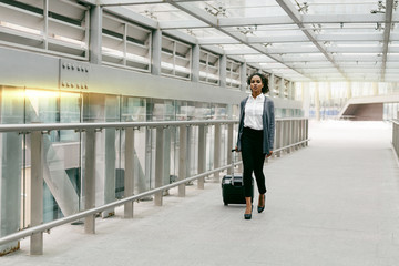 Young woman with luggage walking on terminal, preparing for business trip