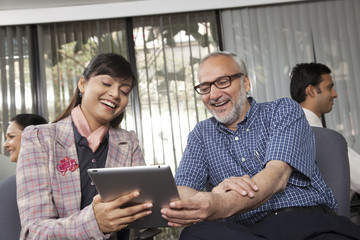 Senior man and woman looking at a tablet