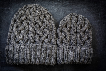 Two sizes of hand knit woolen hats with cables. One for a child, the other for an adult.