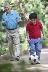 Grandson playing soccer as grandfather watches on
