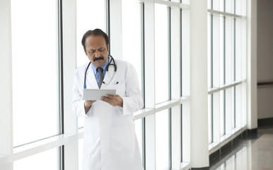 Doctor reading a report on a digital tablet