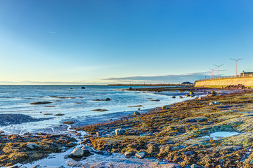 Sunset in Rimouski, Quebec by Saint Lawrence river in Gaspesie region of Canada with rock boulders in shallow water with pier