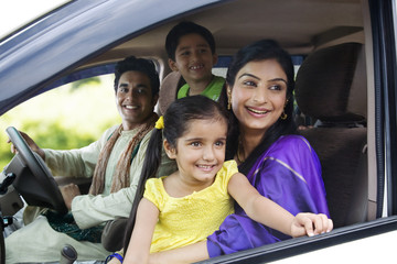 Family sitting inside a car