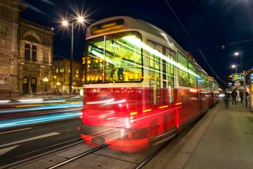 Illuminated Opera house in Vienna, Austria and tram