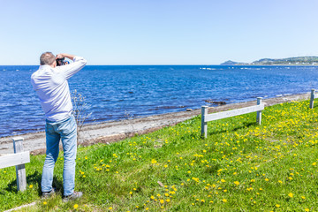 Young fit man photographer taking pictures of Gaspesie coast in Capucins, Quebec, Canada with Saint Lawrence river