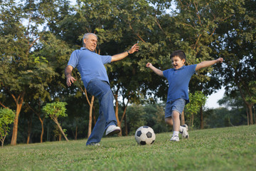 Grandfather and grandson playing soccer