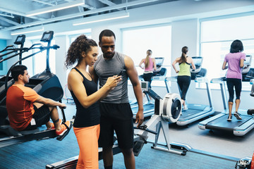 Man and woman looking at a cell phone in the gym