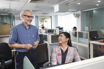 Senior man and woman having a chat in office