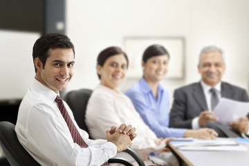 Successful businessman smiling with executives in a meeting