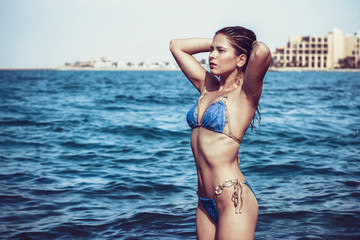 Sexy woman in the blue water looking to the sun