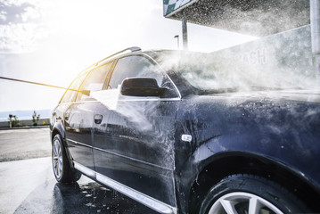 High-pressure washing car outdoors.