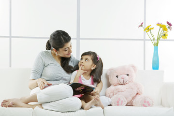 Mother and daughter sitting with a magazine