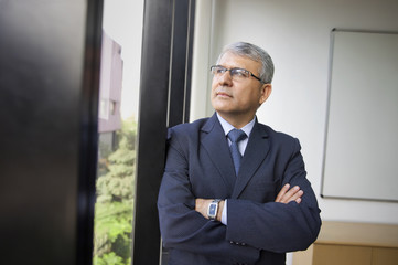 Contemplative mature businessman looking through window at workplace