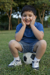 Portrait of a young boy sitting on a football