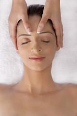 Close-up of beautiful young woman having head massage