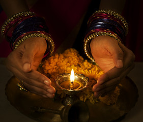 Hands cupped around a diya