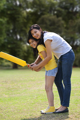 Mother and daughter playing cricket