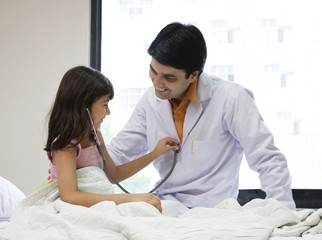 Girl checking a doctors heartbeat