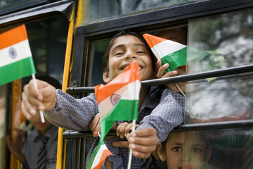 School boys holding the Indian flag in a bus