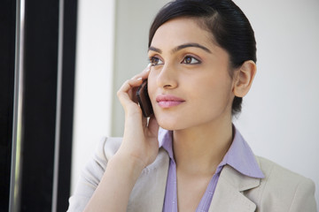 Beautiful businesswoman using mobile phone in office