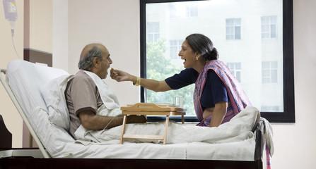 Wife feeding her husband in a hospital