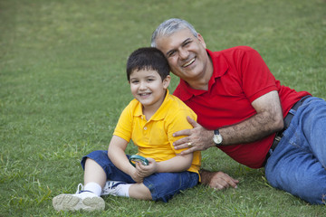 Portrait of young boy with grandfather in a park
