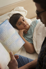 Boy relaxing on the bed while his father is reading him a story