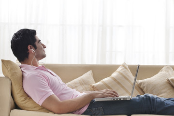 Young man contemplating while listening to music with laptop